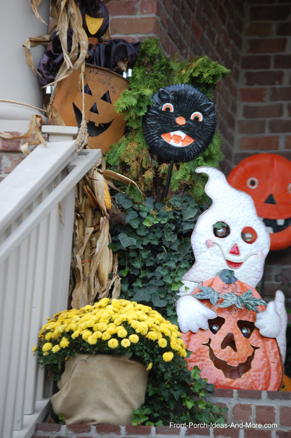 Halloween display on front steps with pumpkin and black cat