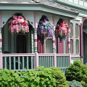 hanging baskets full of colorful flowers on front porch