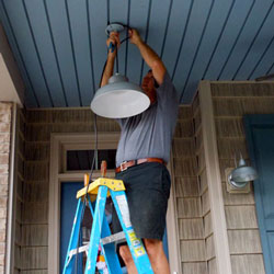 man hanging pendent light on front porch