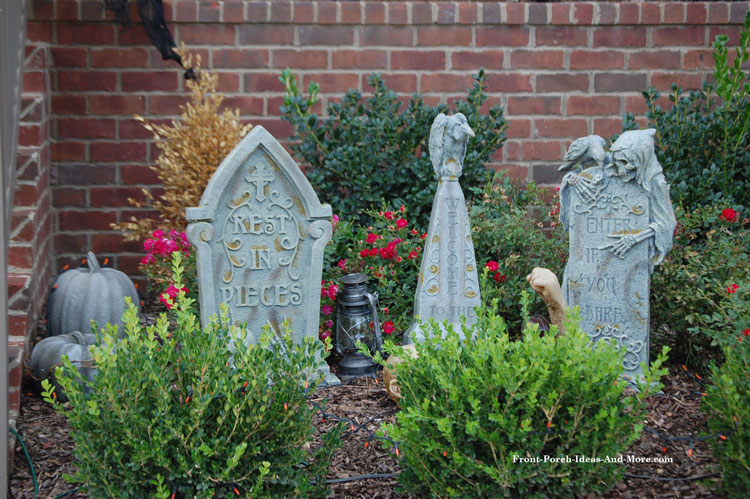 faux graveyard headstones placed amongst front porch landscaping