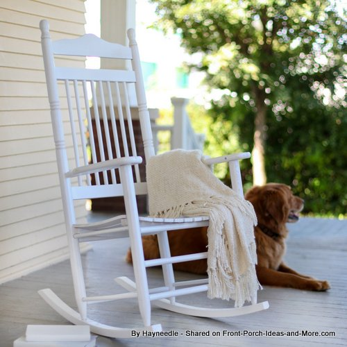 white rocking chair with dog on front porch