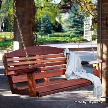 Wooden porch swing in parklike setting with white blanket on it