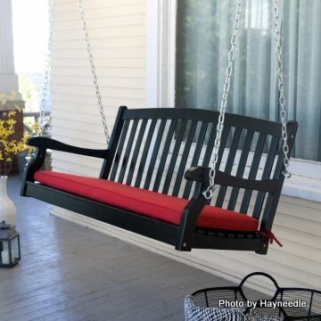 Classic black wood porch swing with a red cushion