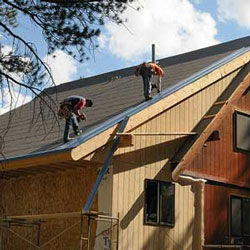 roofers installing a metal roof on a home