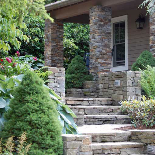 landscaped stone front porch with evergreens