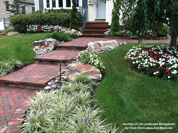 fully landscaped front yard around porch with brick sidewalk