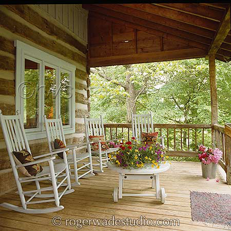 White rocking chairs on porch of beautiful log home