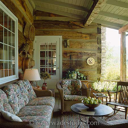 cozy log home side porch with cozy wicker furniture