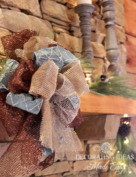Pine garland and burlap bows decorate the fireplace mantel in this log home