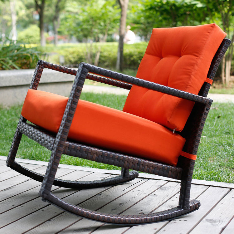 rattan framed rocking chair in brown with orange cushion