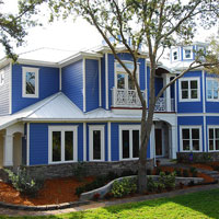 metal roof on blue home with front porch