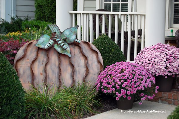 elegant metal pumpkin sculpture with colorful mums in front of porch