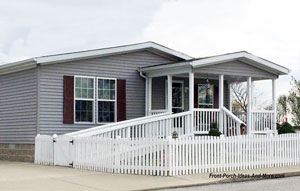gable front porch addition on mobile home with white picket fence