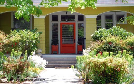 orange front door on yellow porch