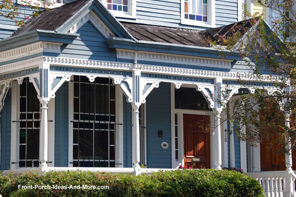 very ornate fretwork on lovely blue front porch