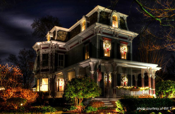 Holiday Wreaths Displayed In Windows Of Victorian Style Home