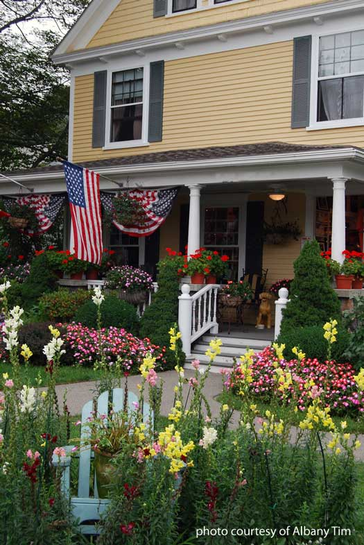 front porch with flowers and flags
