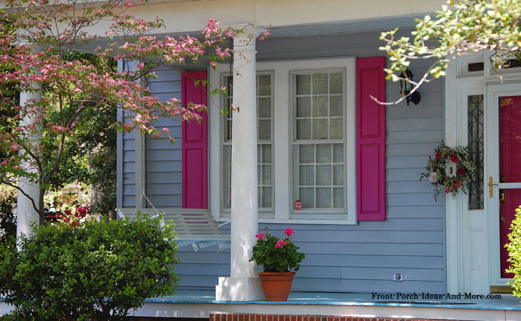 pink porch shutters on open front porch with porch swing in spring