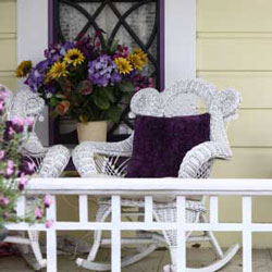 bright porch cushions on front porch wicker chair