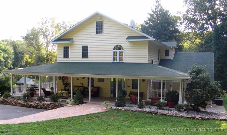 beautiful country style wrap around porch with stone walkway