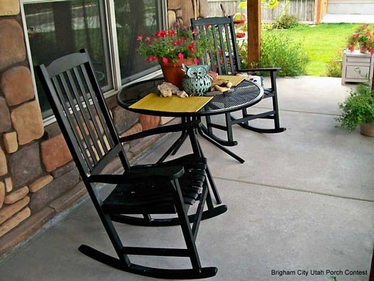 Two Black Rocking Chairs And A Black Side Table
