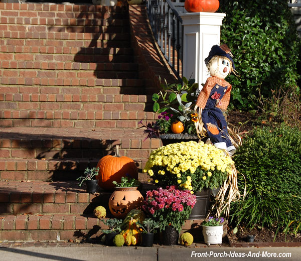 scarecrow and mum array at bottom of porch steps for fall decorations