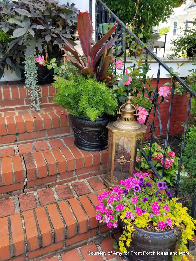 brick porch steps lined with gorgeous flowers