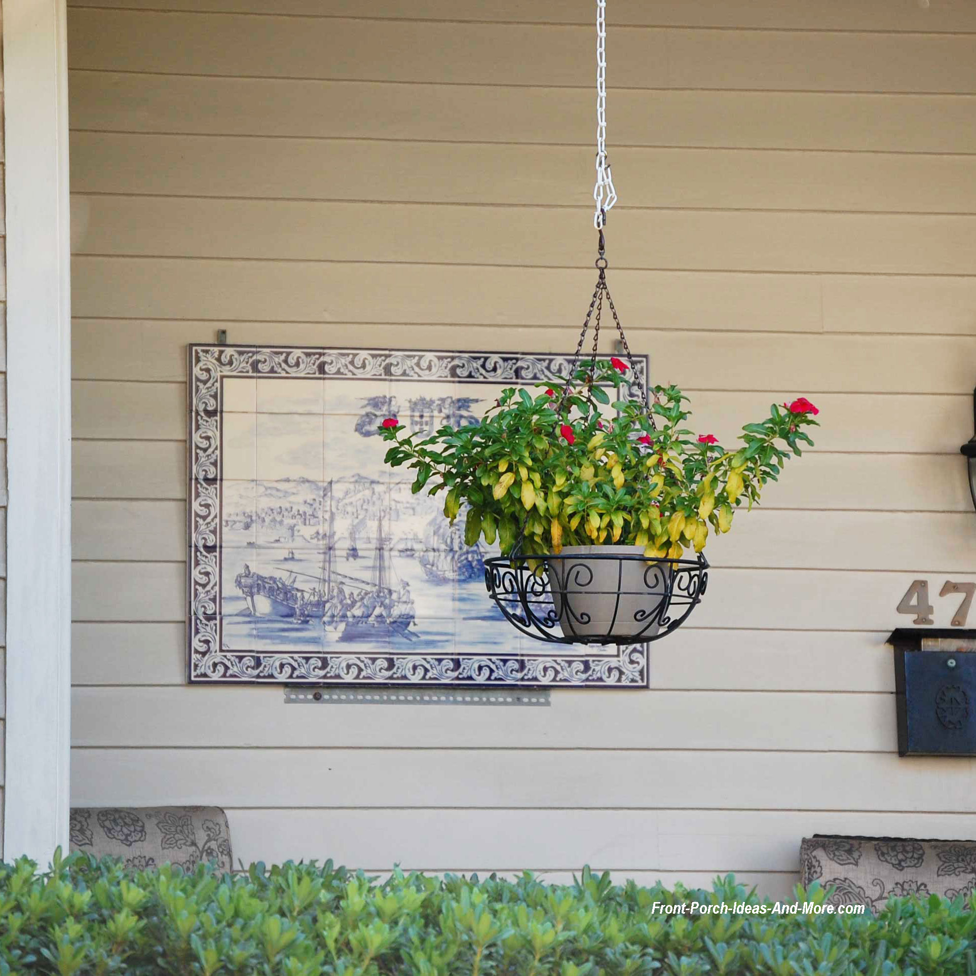 front porch with wall art and hanging basket