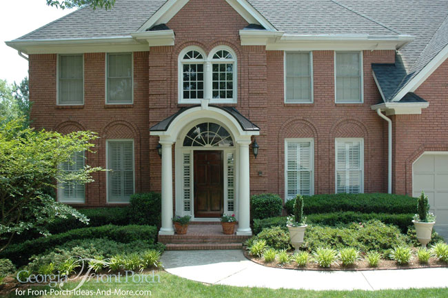 two story brick home with contemporary style portico and standing seam metal roof