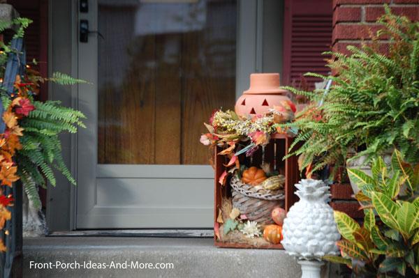 pumpkin on crate with fall foliage on front porch steps