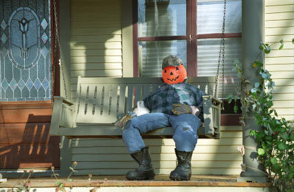 pumpkin scarecrow on porch swing