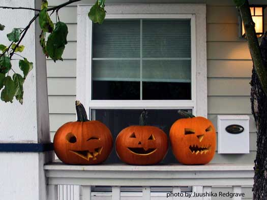 three happy pumpkins on front porch railing