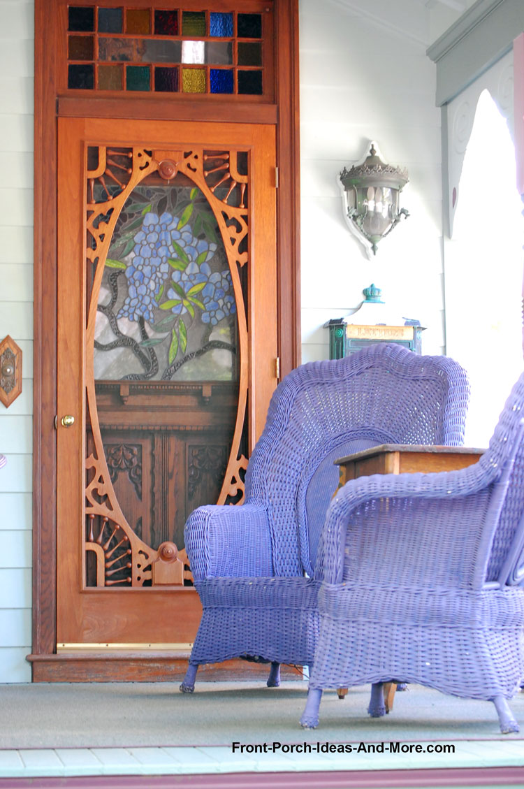 Queen Anne style exterior front door on front porch with purple furniture