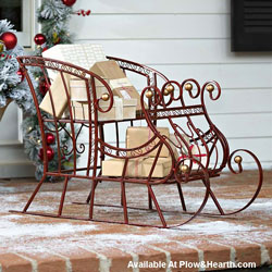classic red metal sleigh on front porch for Christmas