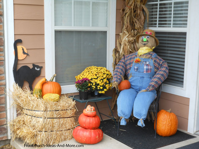 scarecrow and pumpkins on porch steps