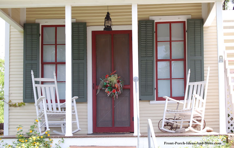 screen door with wreath on front porch with rocking chairs