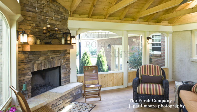 enclosed porch with exposed rafters and stone fireplace hearth