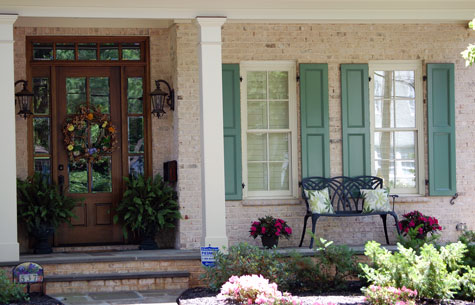 Small front porch with beautiful door, turquoise shutters and lovely garden bench
