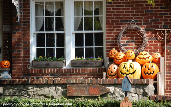 an array of smiling pumpkins on the front stoop