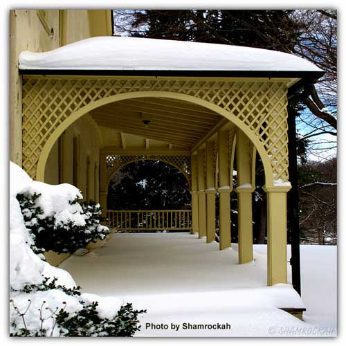 Architecturally beautiful snowy porch on a yellow home - arched entryway