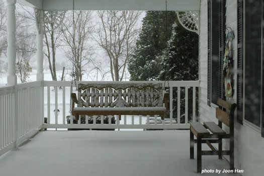 Lovely snowy scene of country style porch in the winter with porch swing