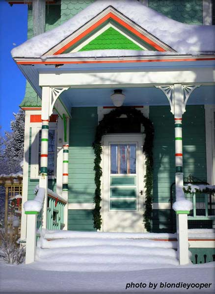 Snow covered porch on this brightly painted gingerbread style home