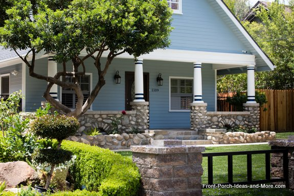 white round tapered porch columns with blue trim and stone balustrade