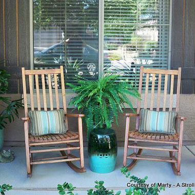 two rocking chairs with planted pot between