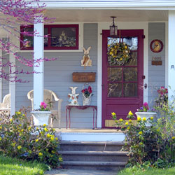 front porch decorated for spring with purples and bunny