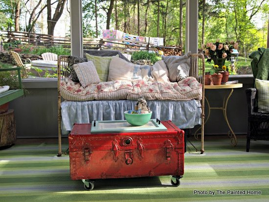 Day bed heaped with soft pillows. Old antique trunk on Denise's screened porch. Set for spring.