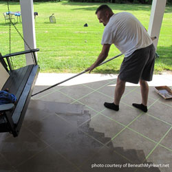 man rolling stain over concrete flooring