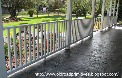 Simple Stamped concrete porch floor with white porch railings