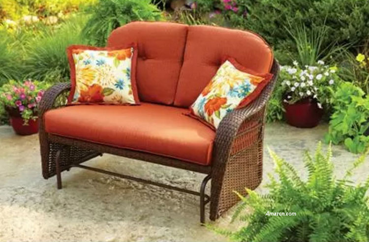 colorful cushions on wicker glidrer on patio