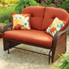 brown wicker glider with orange cushions
